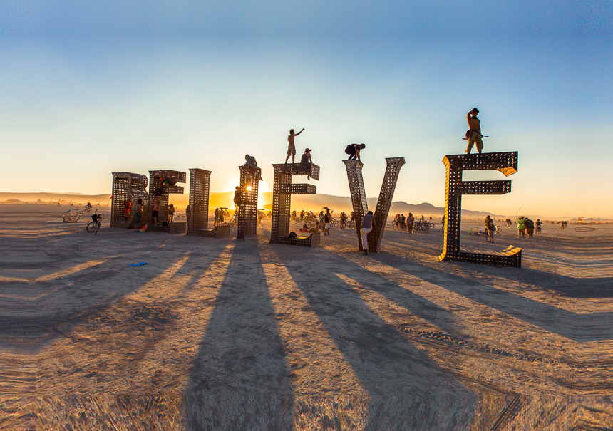a photograph of the believe art installation at burning man 2013 at sunset