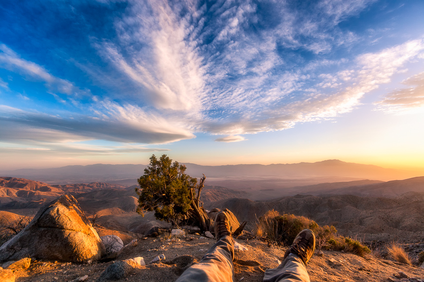 a photograph of feet on the edge of a view point in joshua tree national park during sunset