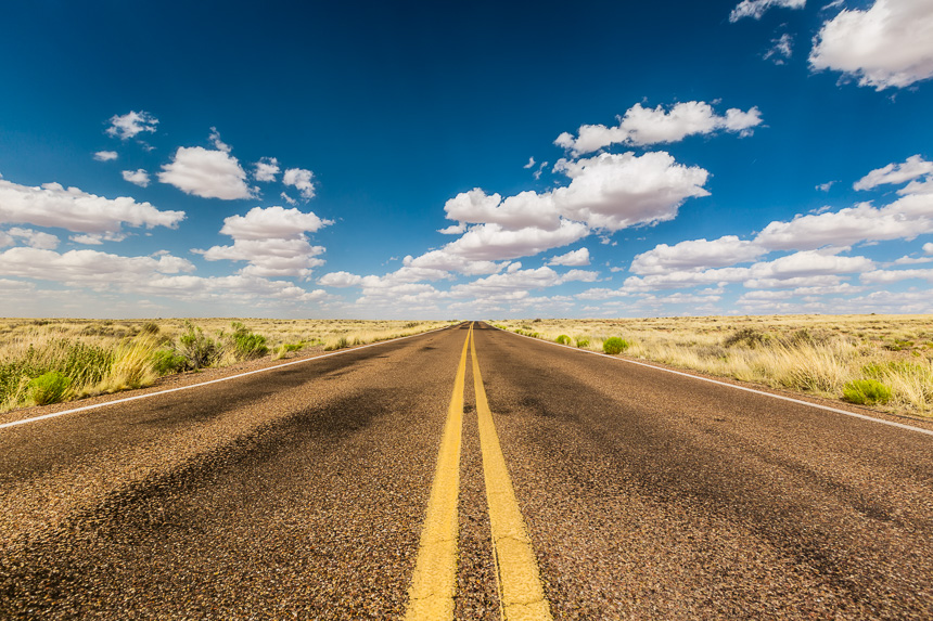 a photograph of an empty road with striping and cumulus clouds on a blue sky