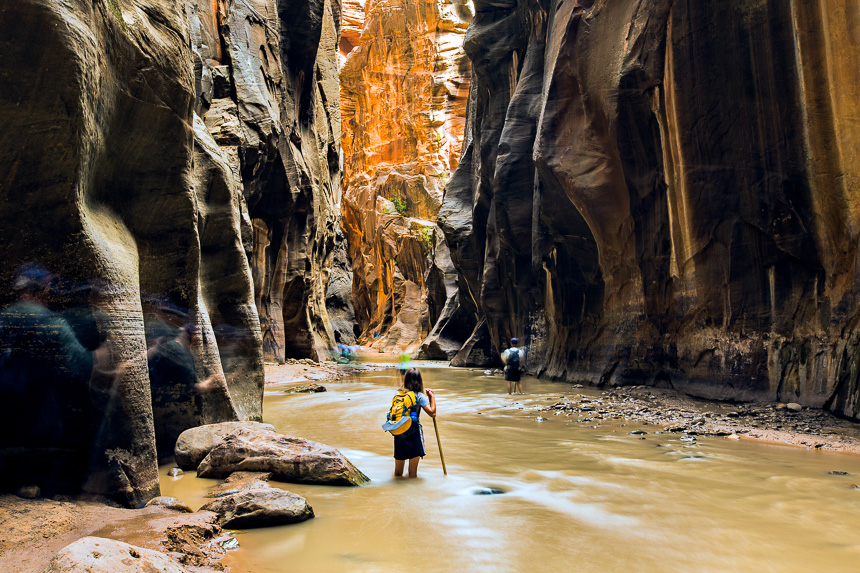 a girl with a walking stick hiking the virgin river narrows in zion national park