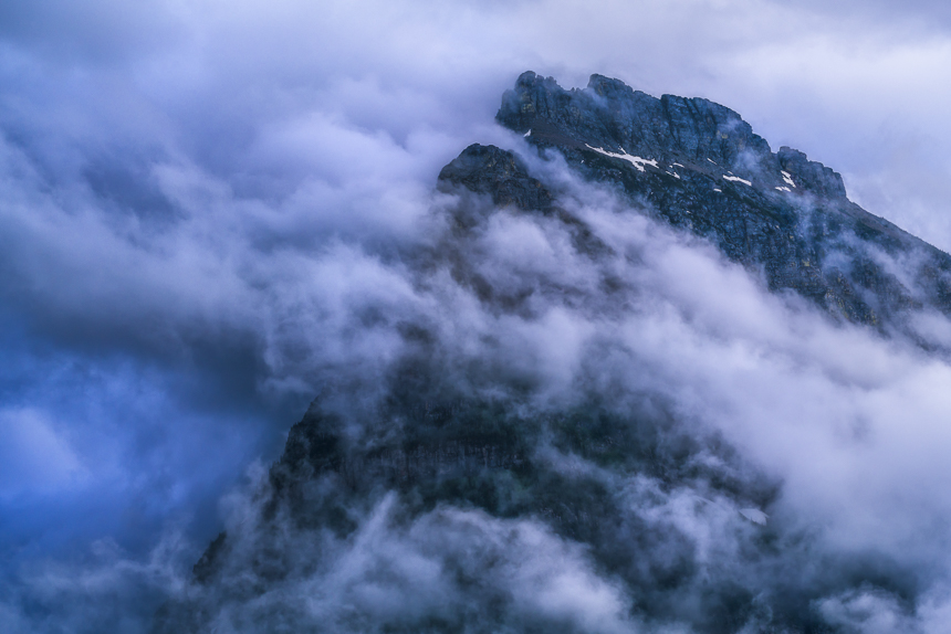 a photograph of mount oberlin in the clouds in glacier national park montana