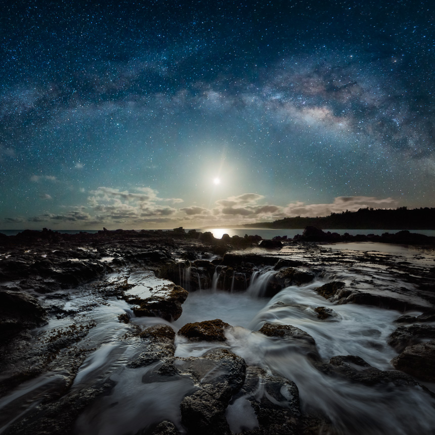 Night photography of the milky way galaxy, moon, and lava tube draining water.