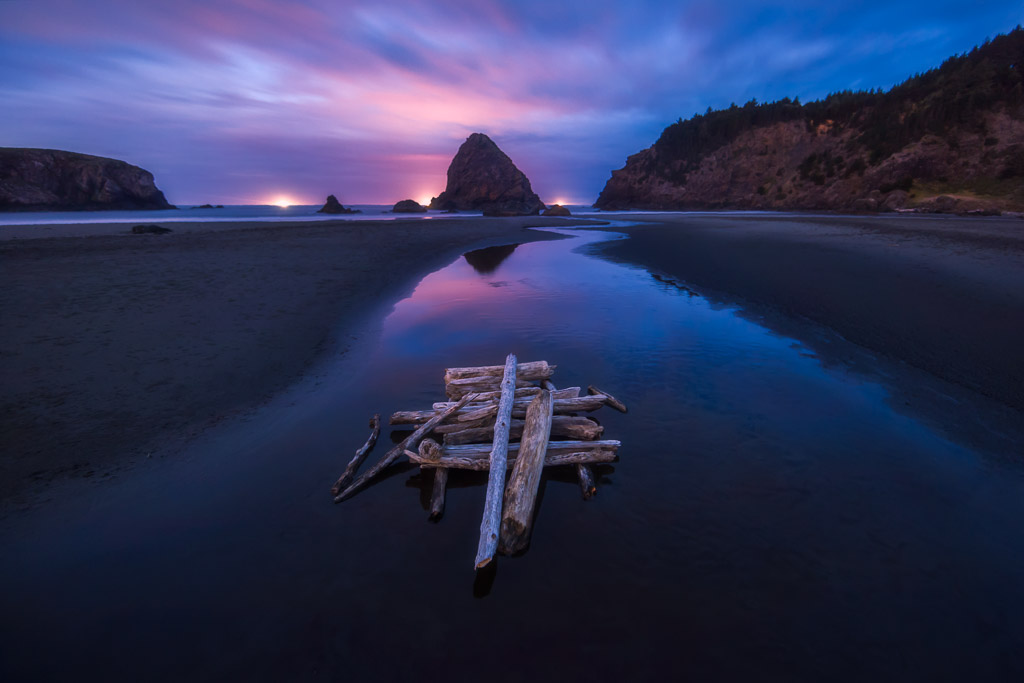 Photo of a stacked logs and a river flowing through a beach towards a sea stack along the oregon coast at twilight