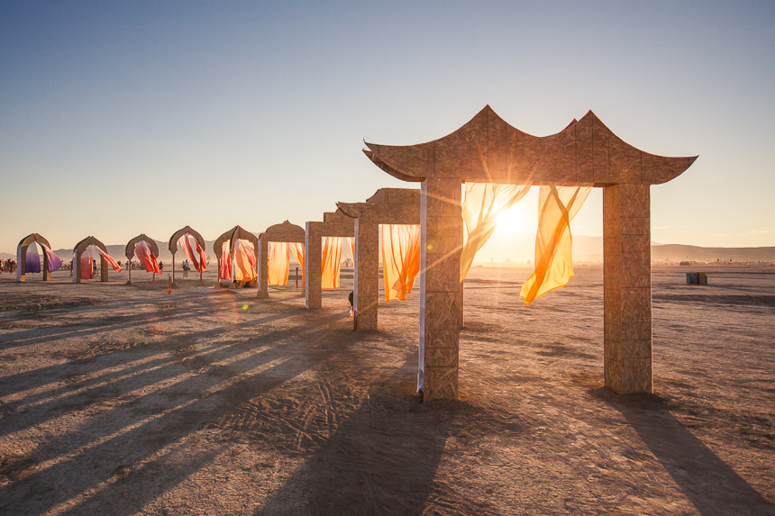 a photograph of the setting sun through one of a series of gates - an art installation at burning man 2014