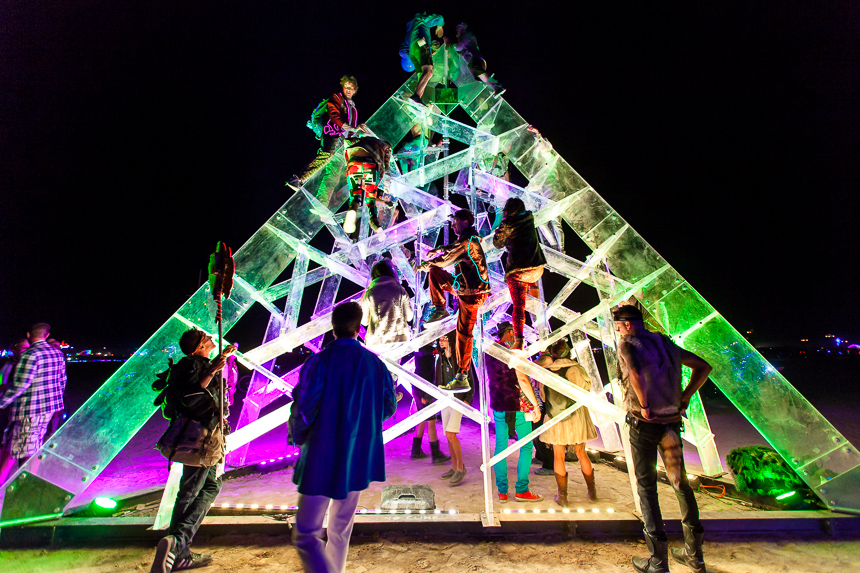 a photograph of people climbing the art sculpture Luz taken at burning man 2014 black rock city nevada