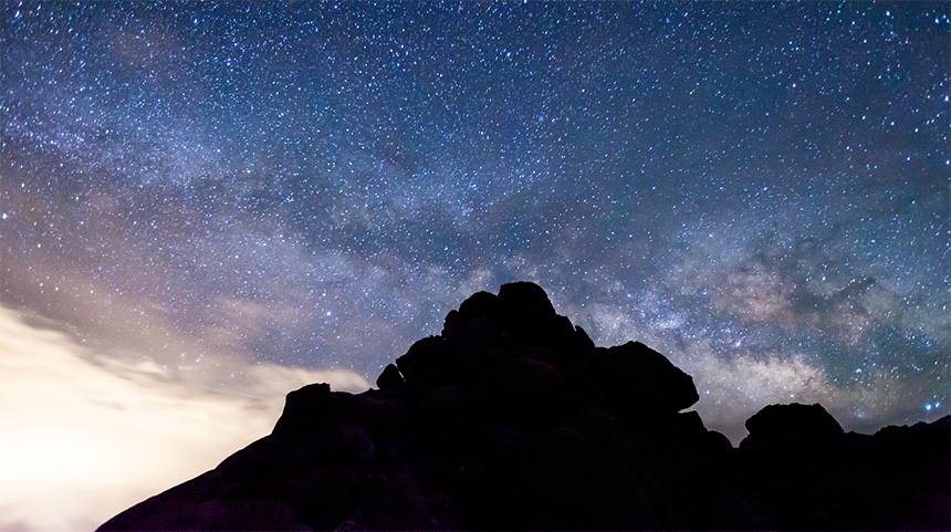 a photograph of the night sky and milky way galaxy over a mountain