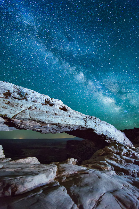 a photograph of the night sky and milky way galaxy at mesa arch in canyonlands, utah