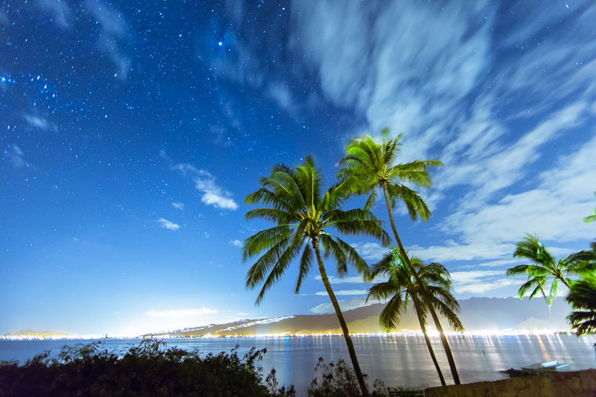a photograph of the night sky and palm trees taken on the island of oahu, hawaii