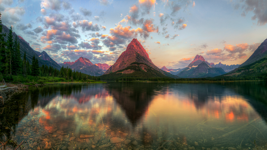 a photograph of a view of swiftcurrent lake with the mountains reflecting on the lake surface