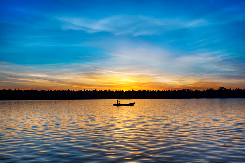 photograph of a man paddling a canoe at sunset at greenlake in seattle, washington