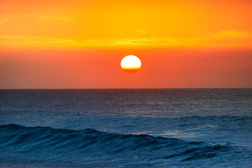 a photograph of the sun setting over the ocean