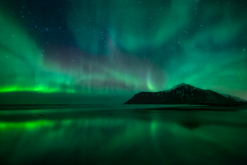 a photograph of the night sky with stars and the aurora borealis reflecting on skagsanden beach in lofoten norway