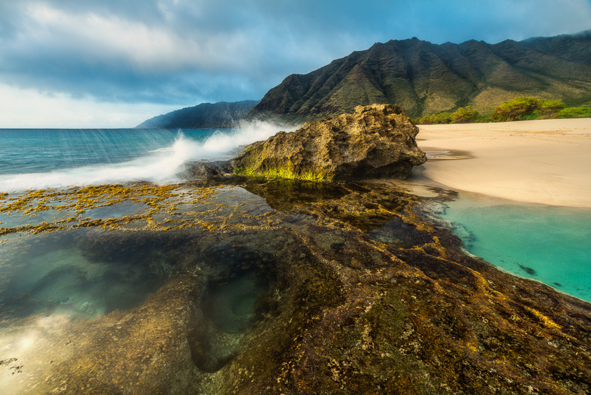 A tropical photo on Oahu of turquoise water tide pools with a wave crashing against a rock.